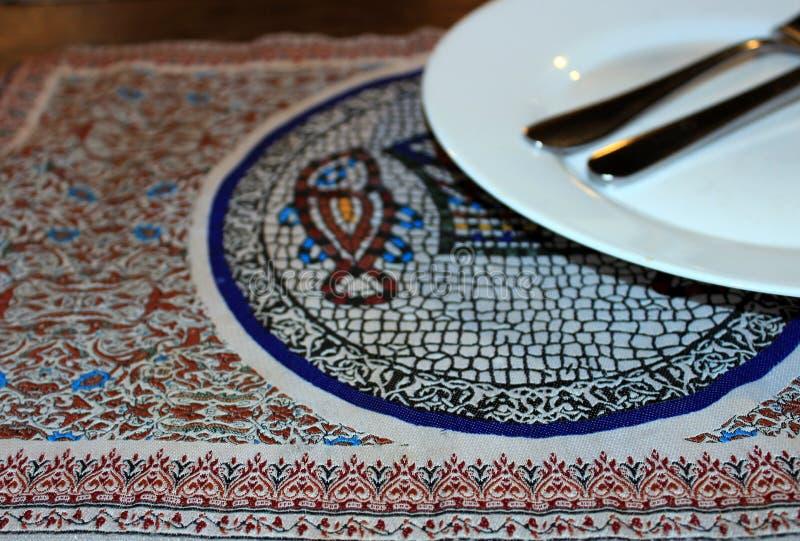 与装饰样式的一块餐巾和一条鱼在中心,与一双白色空的板材和碗筷 免版税库存照片