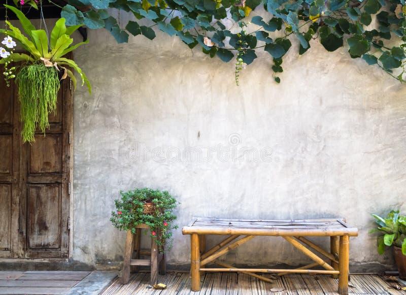与装饰植物的竹长凳混凝土墙背景的 免版税库存图片