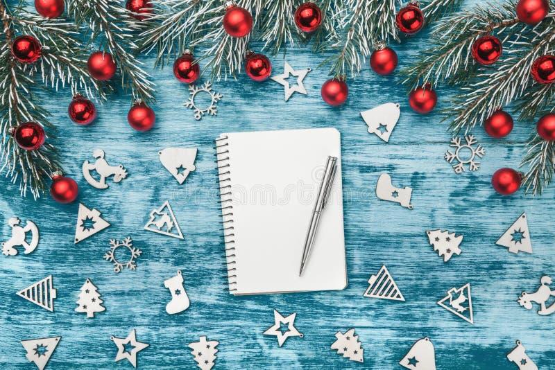 与装饰玩具、空白的笔记薄与笔和冷杉的圣诞节构成在蓝色木背景分支 库存照片