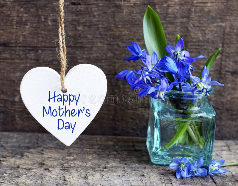 与装饰白色心脏和蓝色春天的愉快的母亲` s天贺卡在老木背景的一个玻璃花瓶开花 免版税库存图片