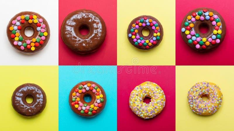 与装饰的巧克力和香草油炸圈饼在明亮的颜色背景,顶视图 库存图片