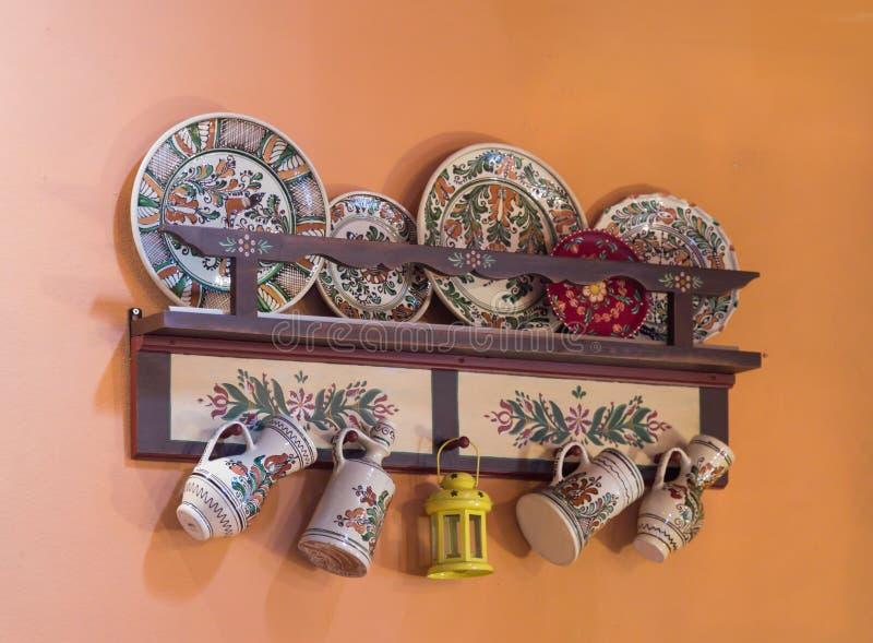 与装饰盘的架子在路旁咖啡馆的墙壁上在Sighisoara镇附近在罗马尼亚 免版税图库摄影
