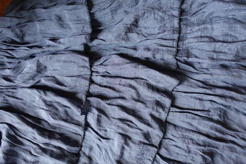 与装饰衣裙3行的灰色蓝色织品  免版税库存照片