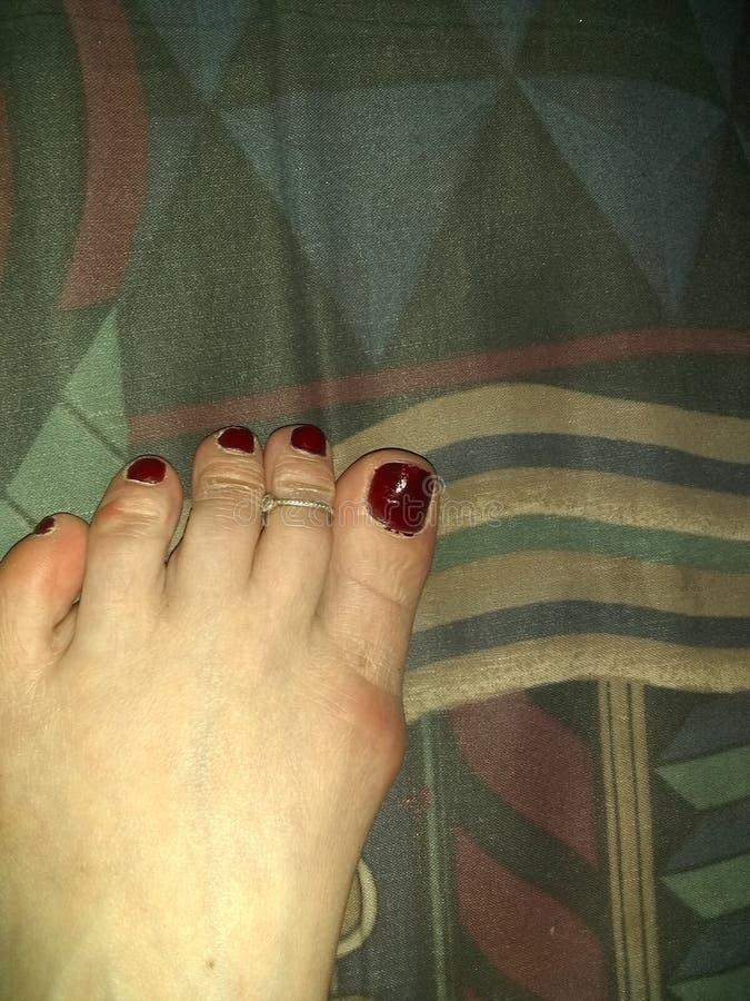 与褐红的红色指甲油的白种人女性脚和纯银脚趾圆环,几何形状在背景中 库存图片