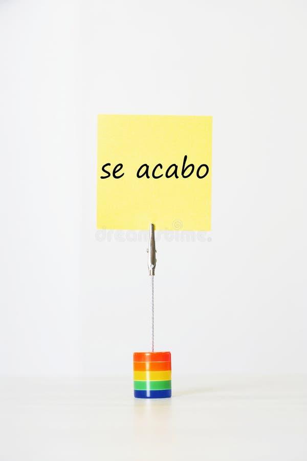与西班牙文本se acabo (它的稠粘的便条结束)被截去对一个多彩多姿的持卡者 图库摄影