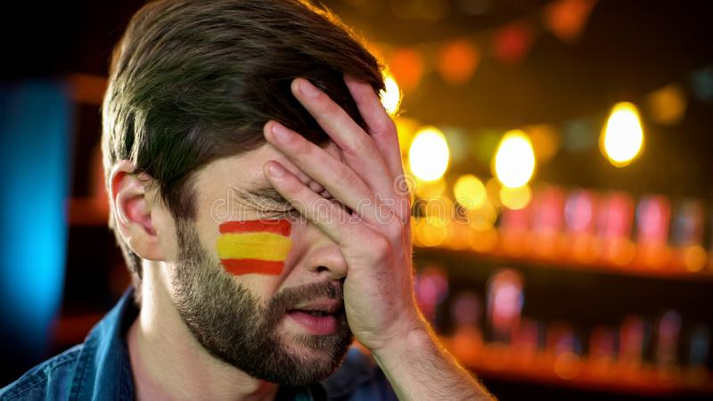 与西班牙旗子的紧张的爱好者在做facepalm的面颊不满意对比赛 免版税库存照片