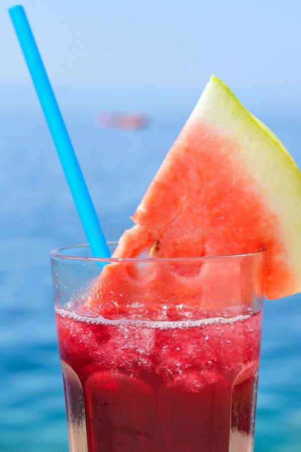 与西瓜切片的水果鸡尾酒在海滩 库存图片