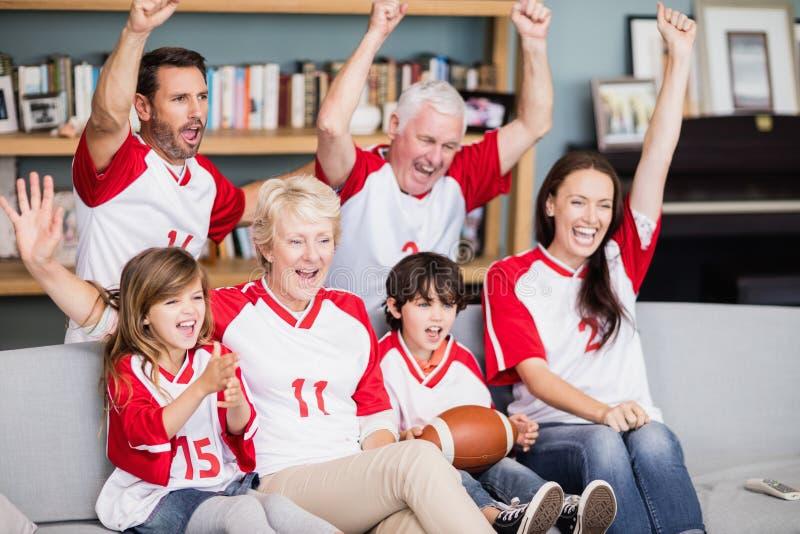 与观看橄榄球比赛的祖父母的微笑的家庭 免版税库存图片