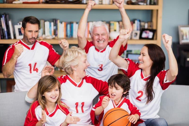 与观看篮球比赛的祖父母的愉快的家庭 图库摄影