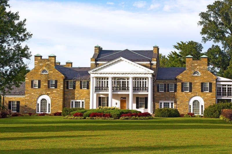 与规则式园林的Glenview历史的豪宅日落的 库存照片