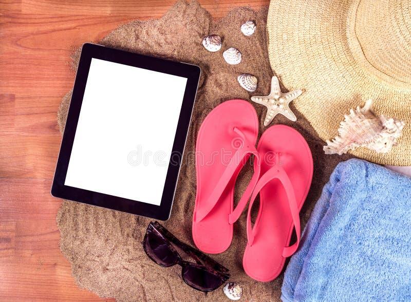 与触发器、毛巾、海星和玻璃的夏天背景与有白色屏幕的数字式片剂计算机 免版税库存照片