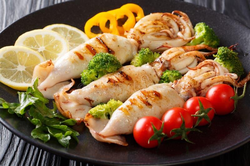 与触手的烤乌贼服务与接近的新鲜蔬菜 免版税图库摄影