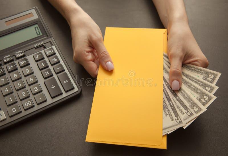 与计算器,在一个黄色信封在女性手上,特写镜头的金钱的企业和赢利概念 库存照片