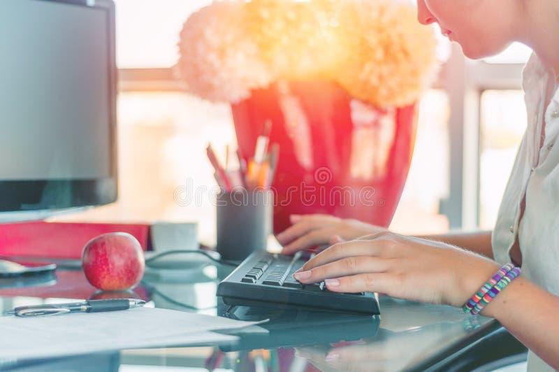 与计算机一起使用在办公室,键入在keyboar的妇女 免版税库存图片