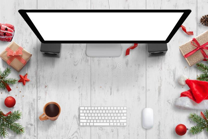 与计算机显示器的圣诞节场面与大模型、键盘、老鼠、茶和圣诞节装饰的被隔绝的屏幕 免版税库存图片