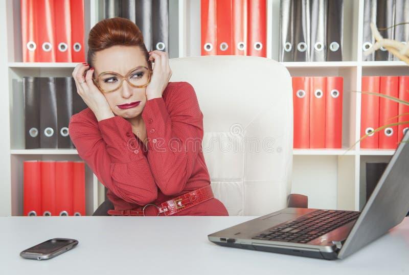 与计算机的女商人害怕的工作 库存照片