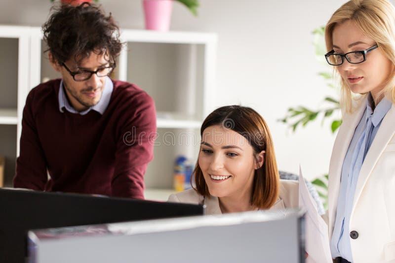 与计算机的愉快的创造性的队在办公室 免版税库存图片