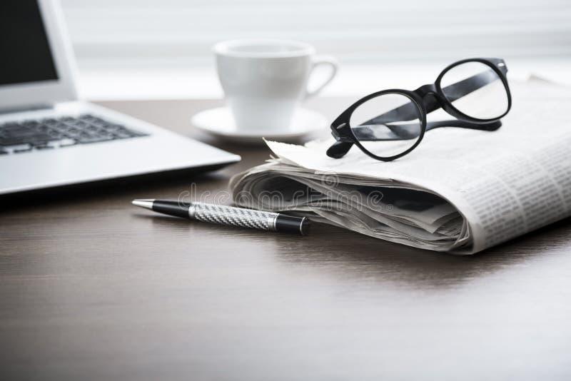 与计算机的报纸在桌上 免版税图库摄影