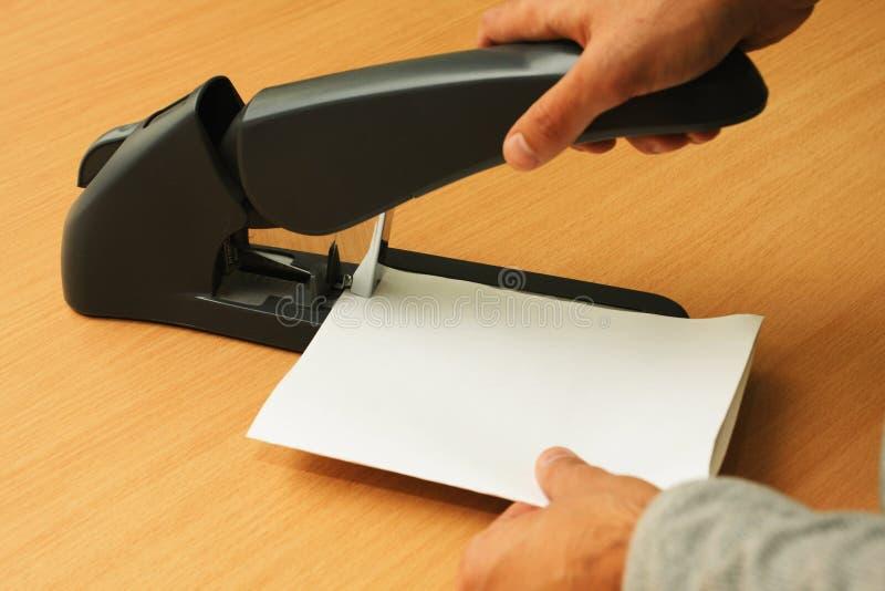 与订书机的约束纸由两只手 免版税库存照片