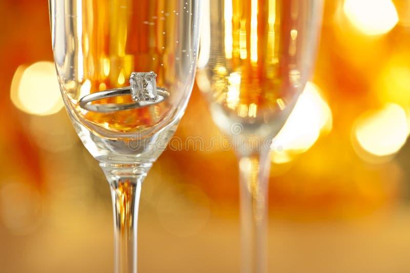 与订婚首饰的香宾玻璃 免版税库存图片