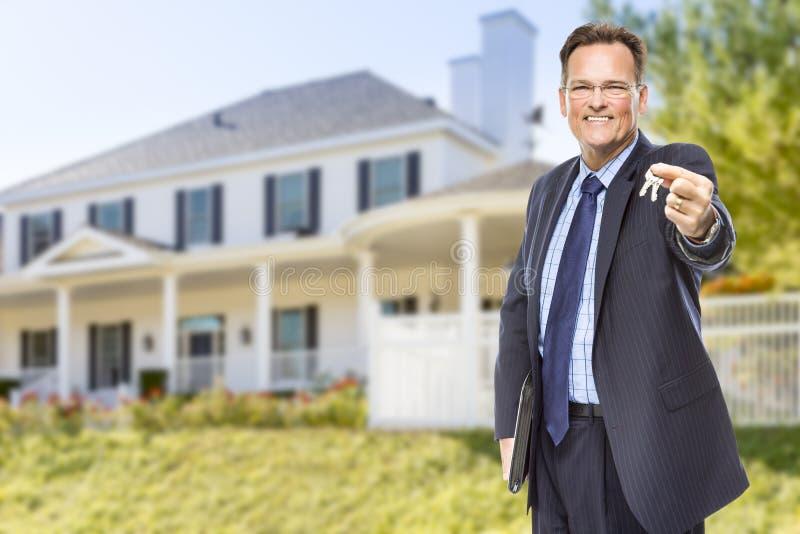 与议院钥匙的房地产开发商在家前面 免版税库存照片
