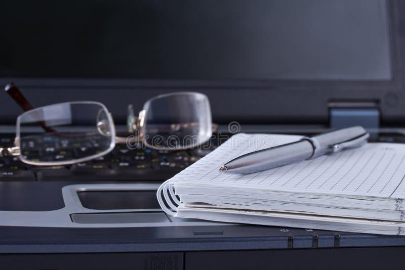 与记事本笔和玻璃位于的黑色笔记本 免版税库存照片