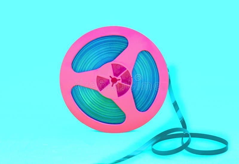 与记录磁带的葡萄酒桃红色音频卷轴在绿色背景 时髦流行艺术样式 库存图片