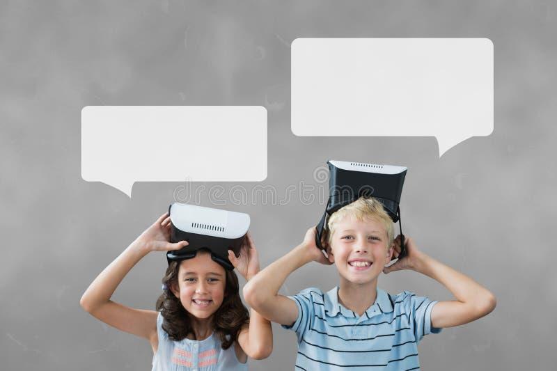 与讲话的孩子起泡拿着VR耳机反对灰色背景 免版税库存照片