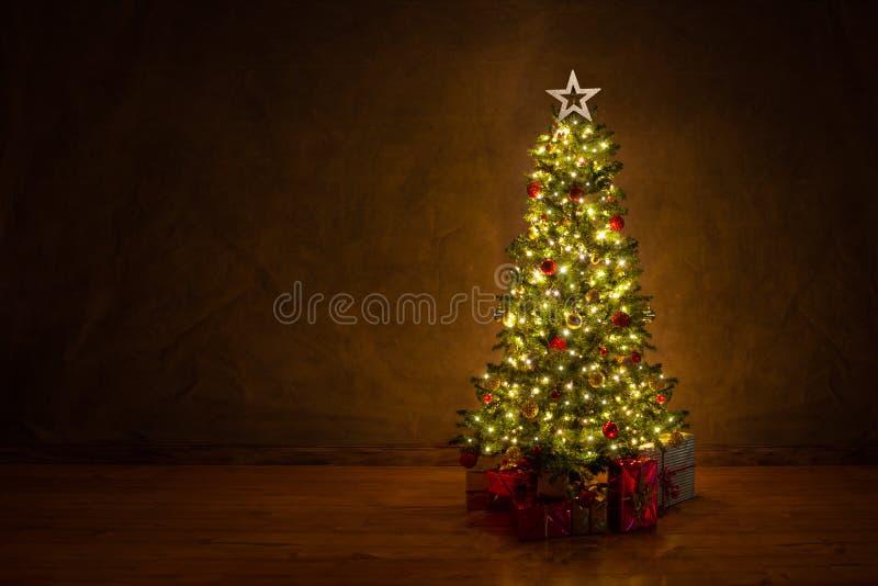 与许多五颜六色的礼品的装饰的圣诞树 图库摄影