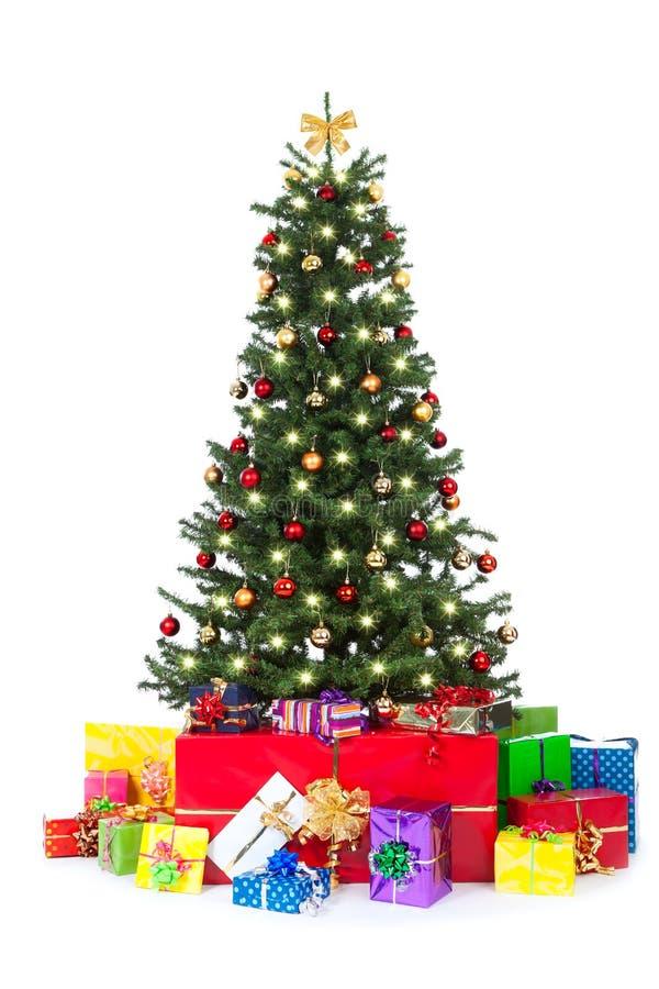 与许多五颜六色的礼品的装饰的圣诞树 免版税库存图片
