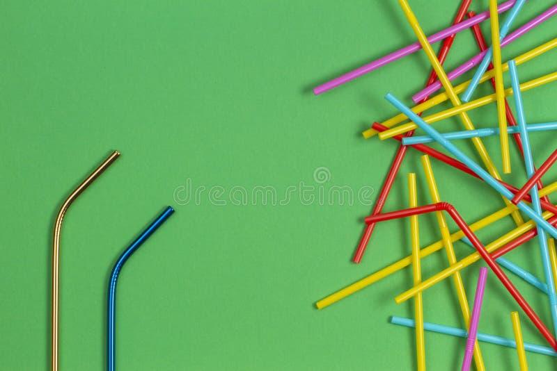 与许多多彩多姿的塑料秸杆的不锈钢可再用的吸管在浅绿色的背景 库存图片