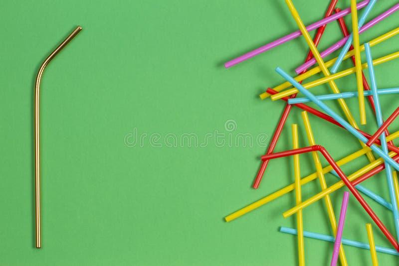 与许多多彩多姿的塑料秸杆的不锈钢可再用的吸管在绿色背景 库存照片