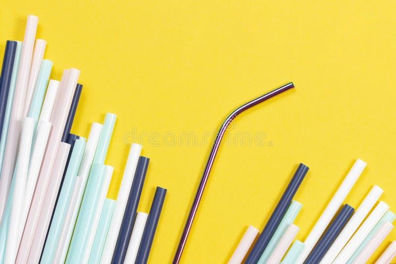 与许多多彩多姿的塑料秸杆的不锈钢可再用的吸管在黄色背景 免版税库存图片