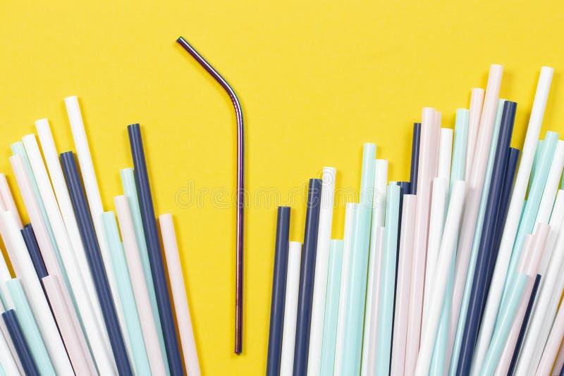 与许多多彩多姿的塑料秸杆的不锈钢可再用的吸管在黄色背景 库存照片