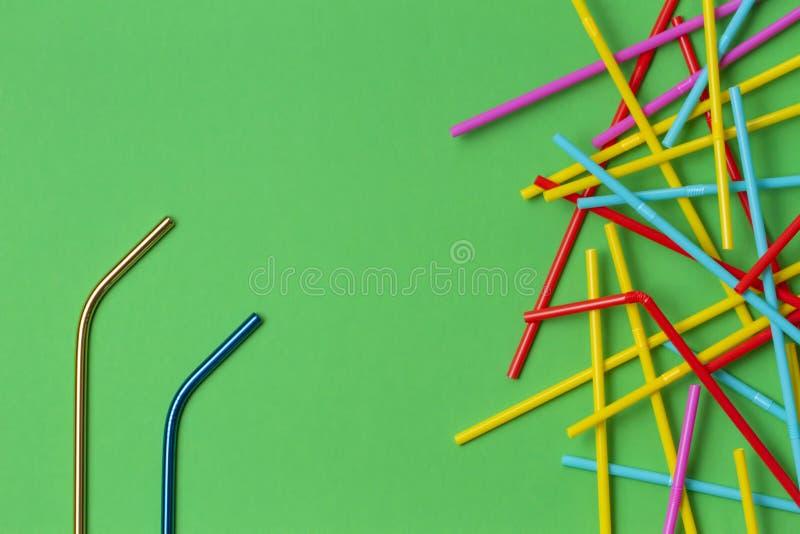 与许多多彩多姿的塑料秸杆的两根不锈钢可再用的吸管在绿色背景 没有塑料,零 图库摄影