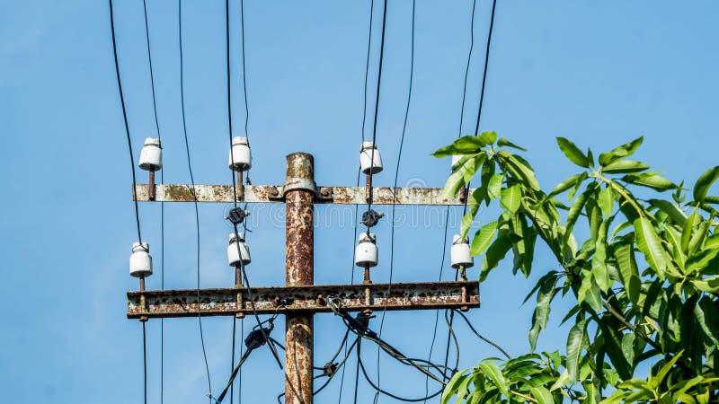 与许多导线和变压器的老生锈的电子杆在树附近 库存图片