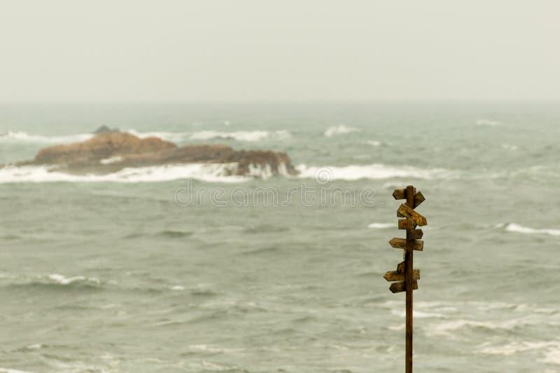 与许多尖的木路标与背景的海 库存照片