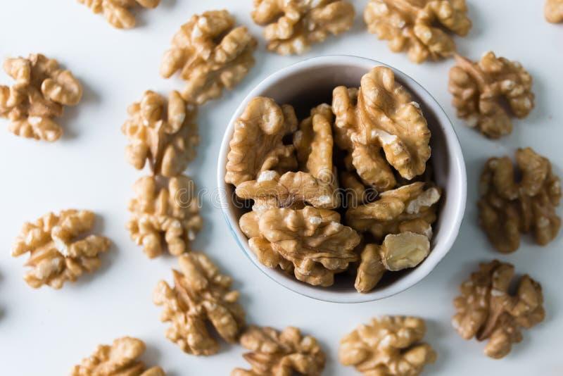 与许多的坚果,核桃,鲜美和健康食物维生素 在碗的核桃在白色木桌上 顶视图 免版税库存图片