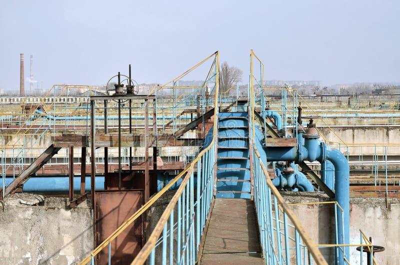 与许多的工业空间管子和通信关于蓝天背景  城市` s水的老水处理厂 免版税库存图片