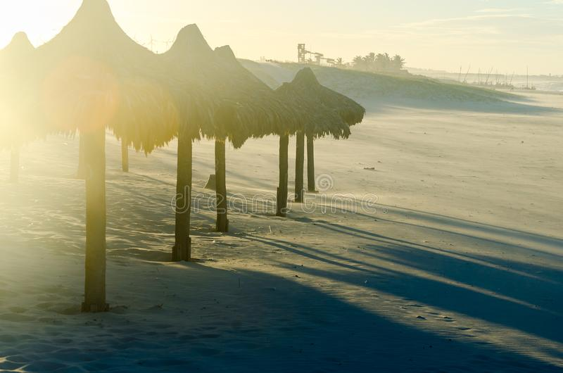 与许多阳伞的被曝光过度的海滩晚上视图 库存照片