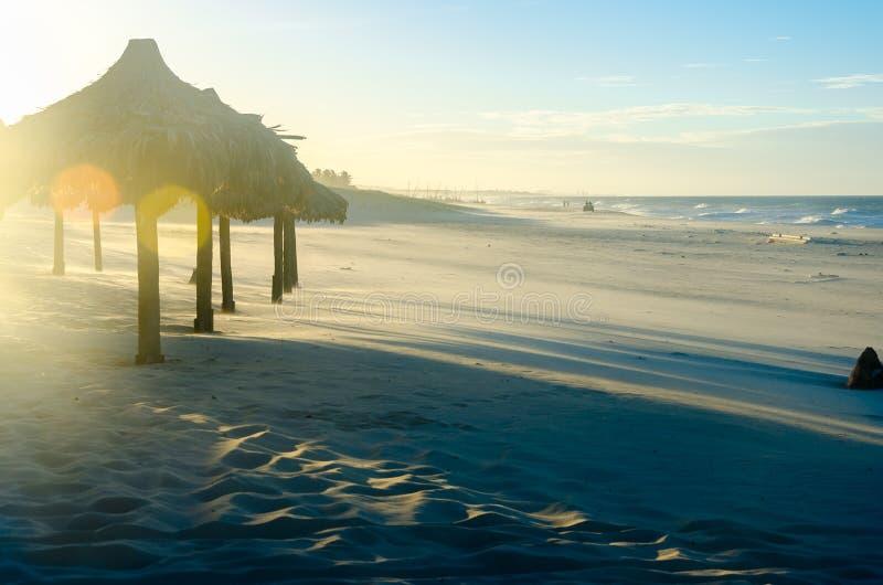 与许多阳伞的被曝光过度的海滩晚上视图 免版税库存图片