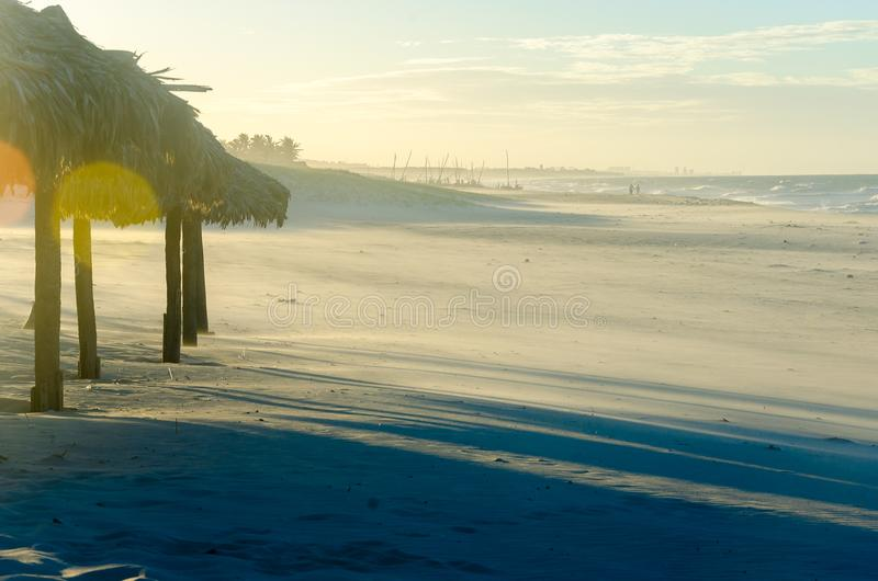与许多阳伞的被曝光过度的海滩晚上视图 免版税库存照片