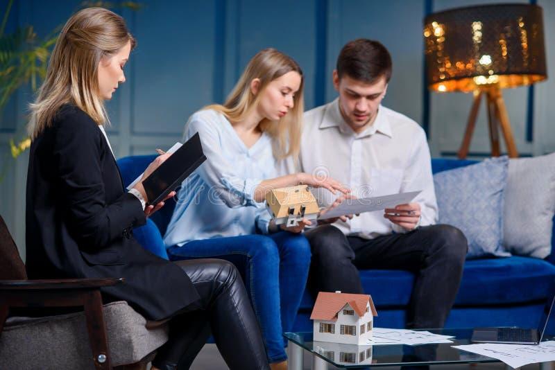 与设计师的年轻白种人家庭会议的在现代蓝色办公室 免版税库存图片