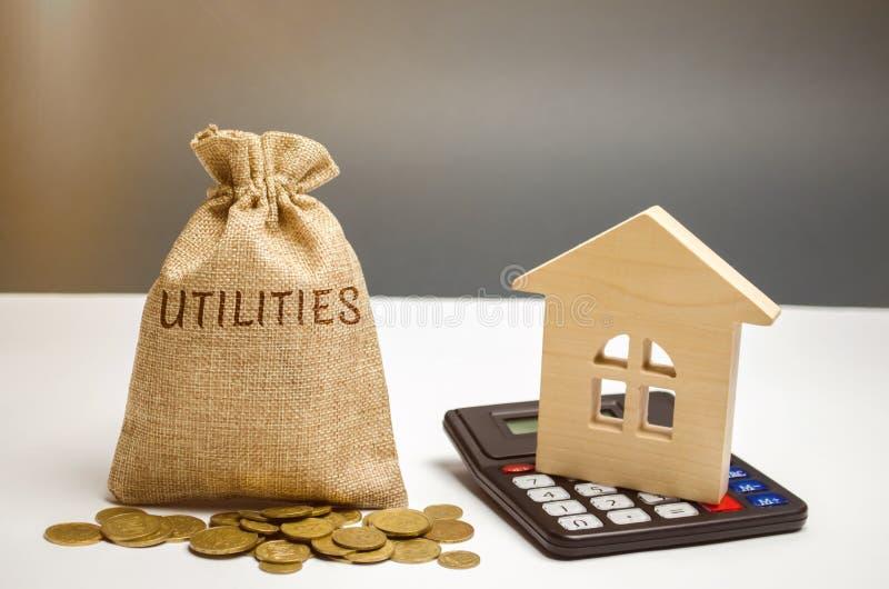 与词公共事业和一个木房子的金钱袋子 攒钱的概念公共事业的付款的 储积 免版税库存照片
