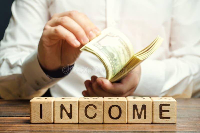 与词收入的木块和金钱在商人的手上 收支分析的概念在公司中 ? 库存图片