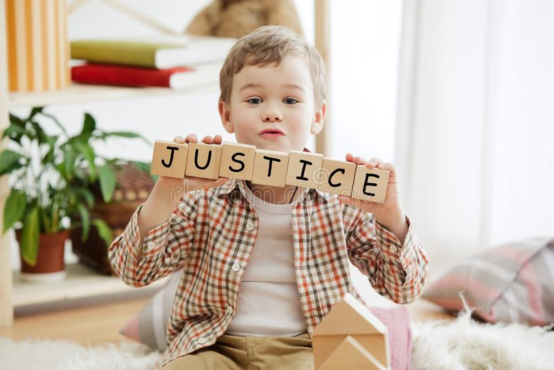 与词正义的木立方体在小男孩的手上 库存图片