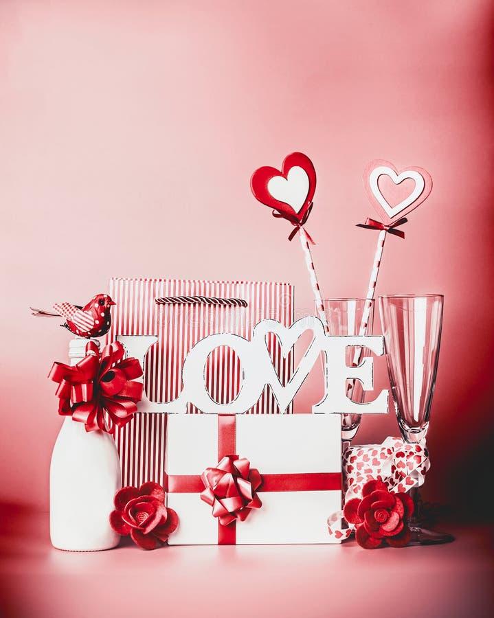 与词爱和问候设置的情人节浪漫静物画:香槟、礼物盒、丝带、心脏和装饰在红色 免版税图库摄影