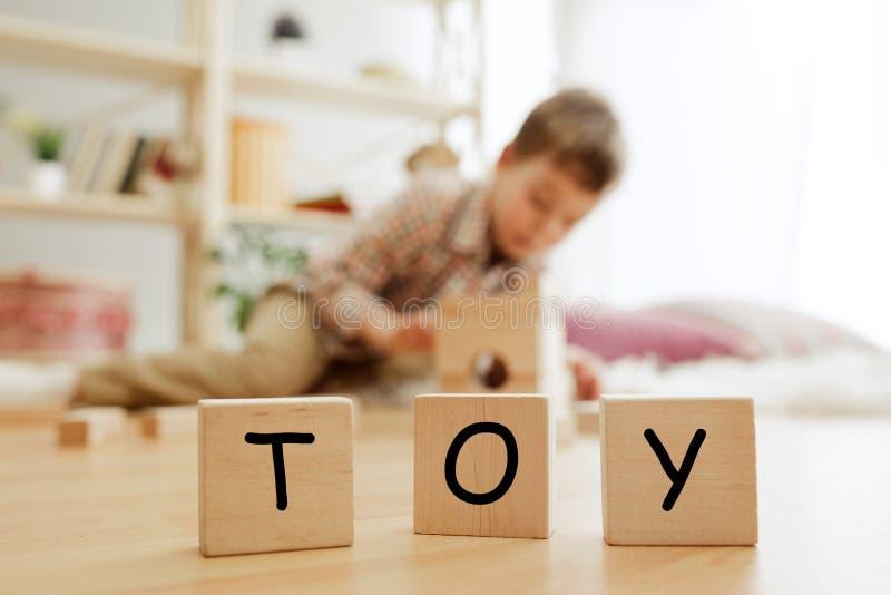 与词玩具的木立方体在小男孩的手上 免版税库存照片