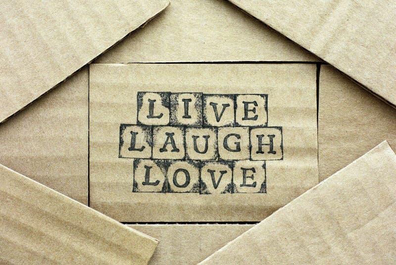 与词的纸板卡片居住笑爱 免版税库存照片
