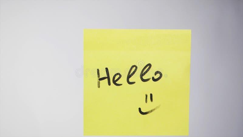 与词的贴纸你好在玻璃 你好-在纸备忘录,企业概念的题字 免版税库存照片
